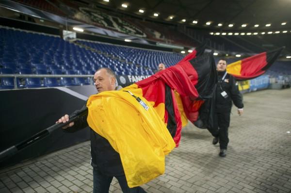Operarios retiran las últimas banderas durante el desalojo del estadio de Hannover (Alemania). / REUTERS