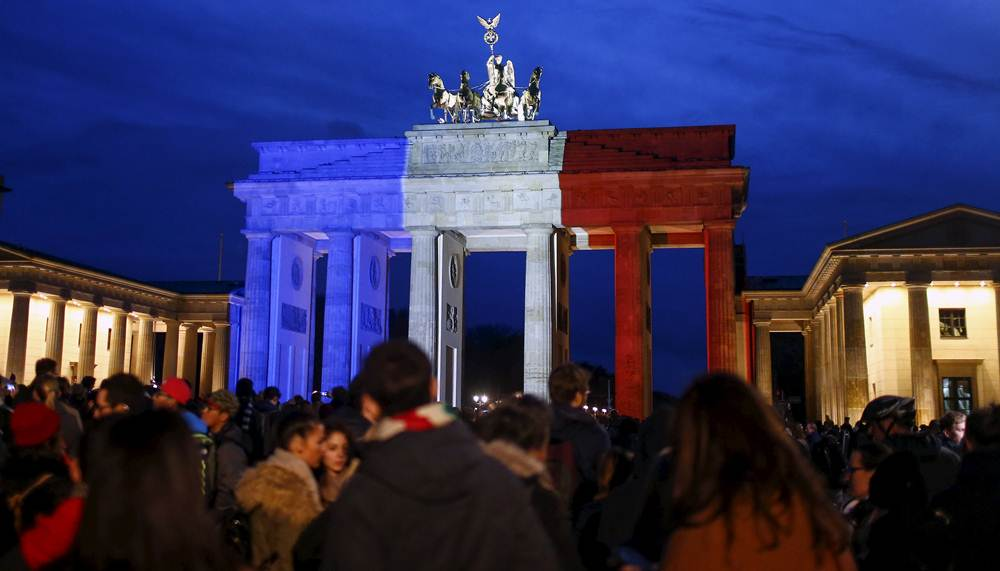 People stand in front of the Brandenburg gate, which is illuminated in blue, white and red in the colors of the French flag in tribute to victims of Friday's attacks in Paris, in Berlin