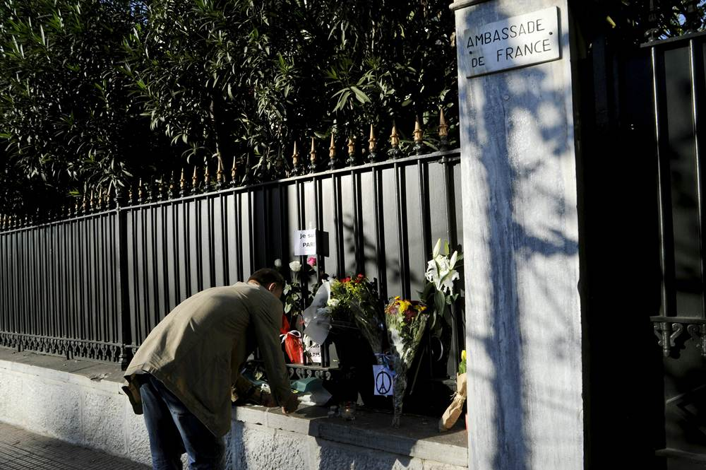 A man lights a candle next to flowers placed in memory of victims of the deadly attacks in Paris, outside the French embassy in Athens
