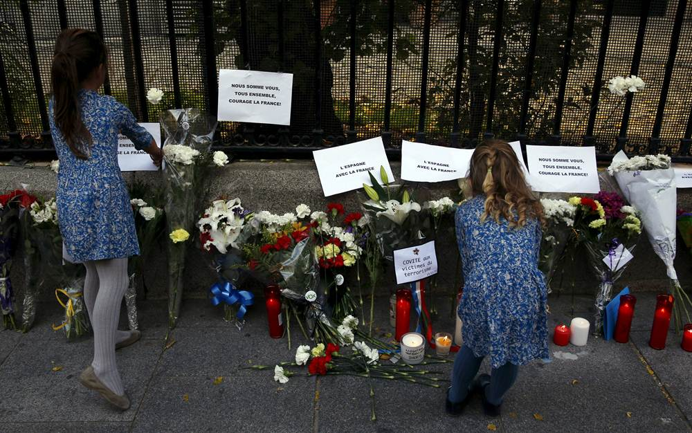 Women place papers next to candles and flowers in memory of victims of deadly attacks in Paris, outside the French embassy in Madrid