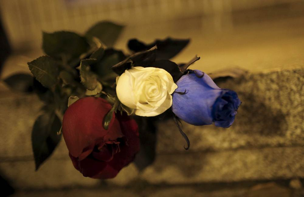 Blue, white and red roses, in the colors of the French flag, lie on the ground in tribute to the victims of Paris attacks in Tbilisi