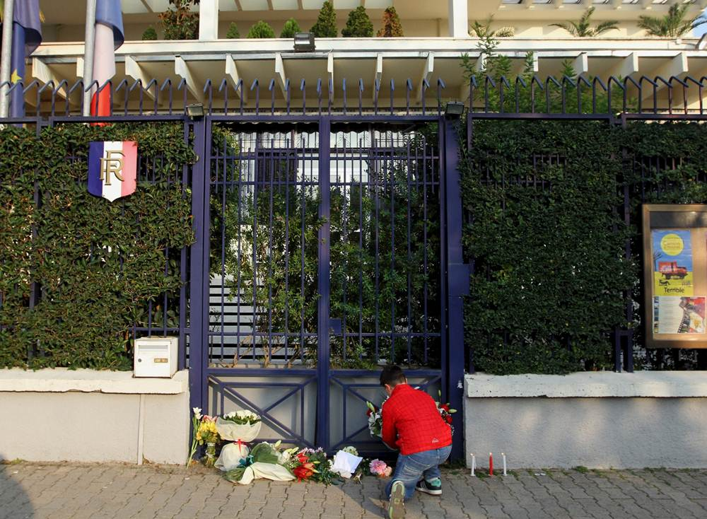 A boy puts flowers in front of the French embassy to commemorate victims of the Paris attacks, in Tirana