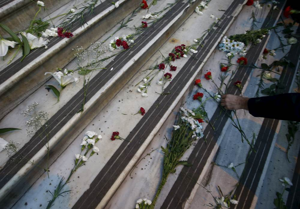 A man leaves flowers as a tribute following the deadly attacks in Paris, outside the French consulate in Istanbul, Turkey