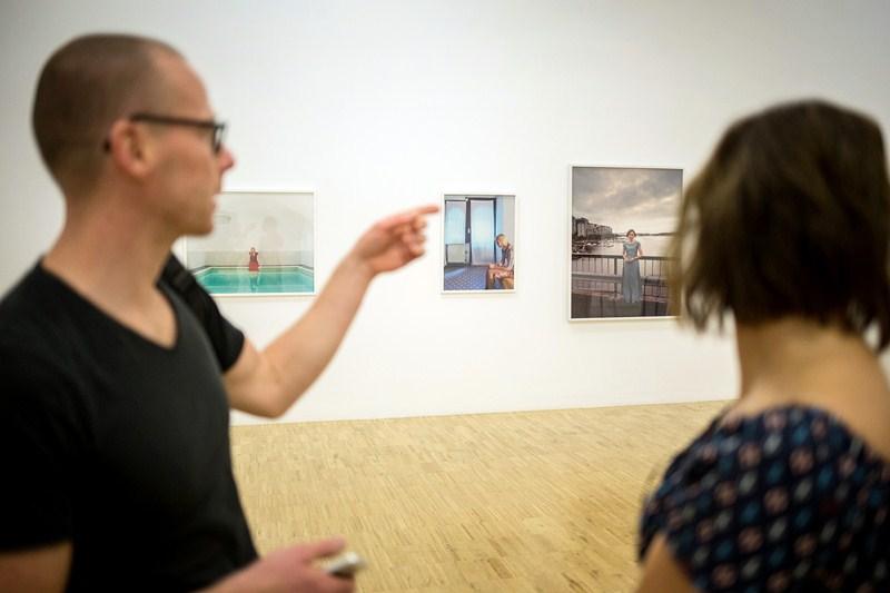 Harri Paliranta, ayer, junto a alguna de las imágenes de la colectiva Gestos hacia uno mismo. / ANDRÉS GUTIÉRREZ
