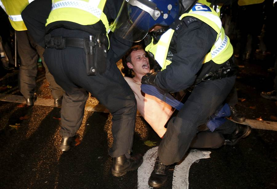 A supporter of the activist group Anonymous is detained by police officers during a protest in London.