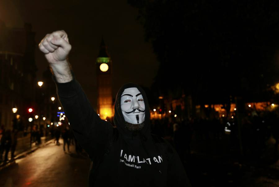 A supporter of the activist group Anonymous gestures during a protest in London