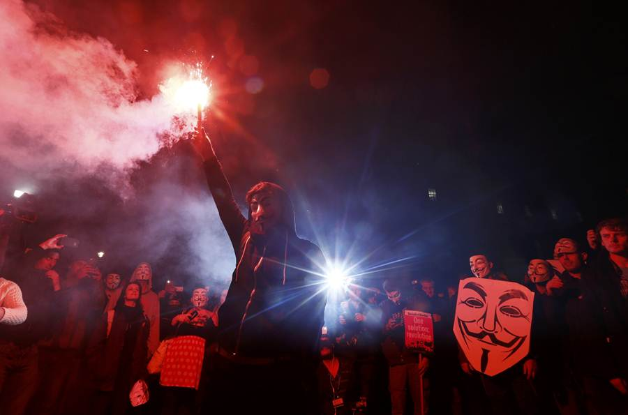 A supporter of the activist group Anonymous holds a flare during a protest in London