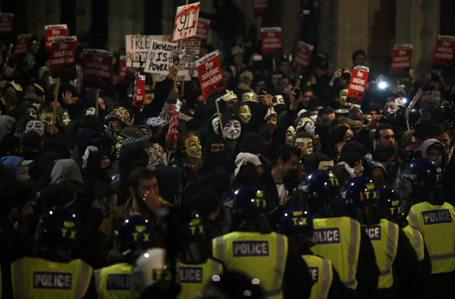 Supporters of the activist group Anonymous face police lines during a protest in London