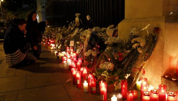 Una mujer y una niña muestran respeto por las víctimas en la embajada francesa de París. | REUTERS