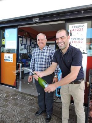 José Miguel González y su hijo José Ángel, descorchando una botella de sidra tras conocer que había caído también un cuarto premio. | NORCHI
