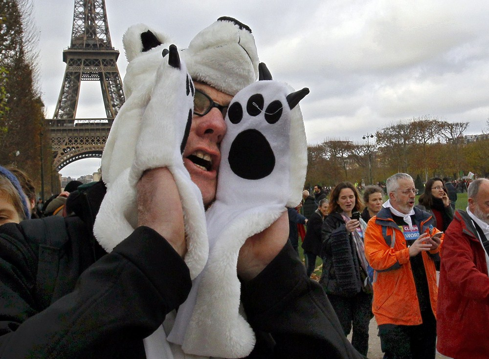 An environmentalist wears a polar bear costume as he participates in a protest near the Eiffel Tower in Paris as the World Climate Change Conference 2015 (COP21) continues near the French capital in Le Bourget