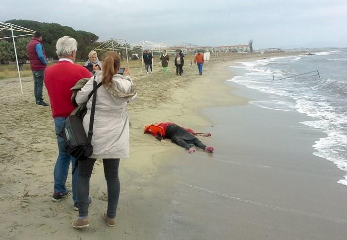 Varias personas observan el cuerpo sin vida de un refugiado en una playa de Ayvalik. | REUTERS