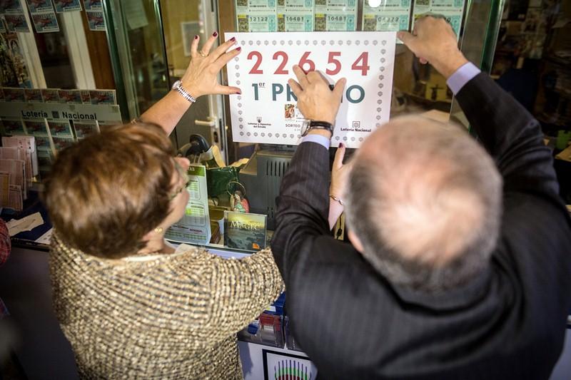 La propietaria del Bazar Mary celebra junto al delegado provincial de Loterías, el alcalde (d) y varios vecinos el primer premio concedido. / ANDRÉS GUTIÉRREZ