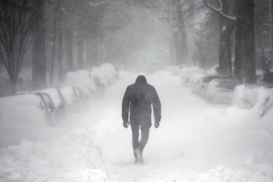 A man walks along a street covered by snow during a winter storm in Washington