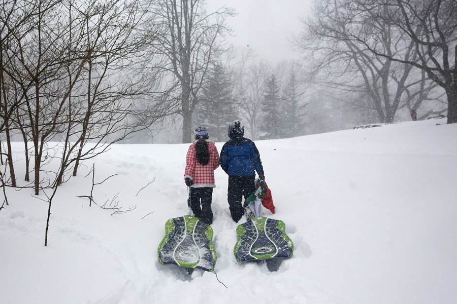 Children carry snow saucers up a hill during a snowstorm at Central Park in the Manhattan borough of New York