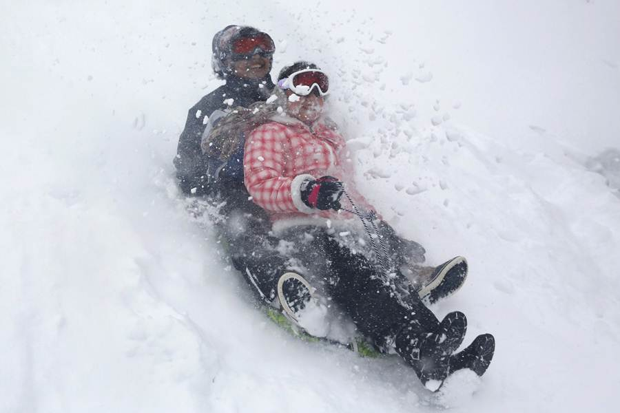 Children ride a snow saucer during a snowstorm at Central Park in the Manhattan borough of  New York