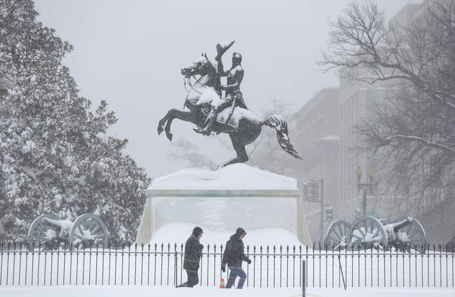 People walk past the statue of Pierre Charles L'Enfant during a winter storm in Washington
