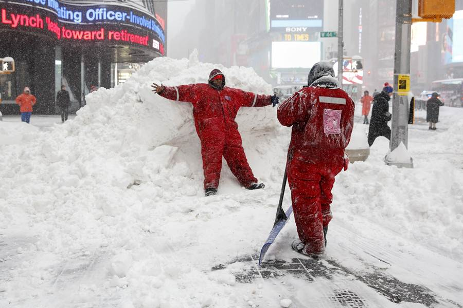 Members of the Times Square Alliance snow clearing team take a photo on a snowbank at Times Square in the Manhattan borough of  New York