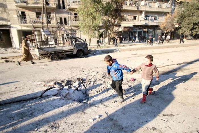 Niños jugando junto a los restos de un bombardeo en Alepo./ ABDALRHMAN ISMAIL / REUTERS